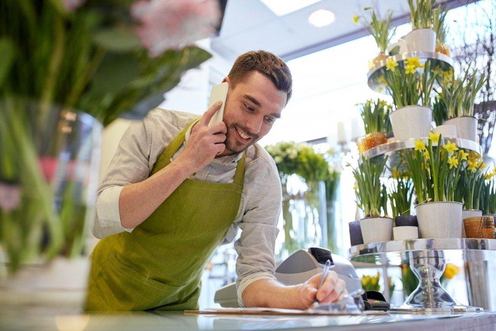 Guy at the flowershop taking orders