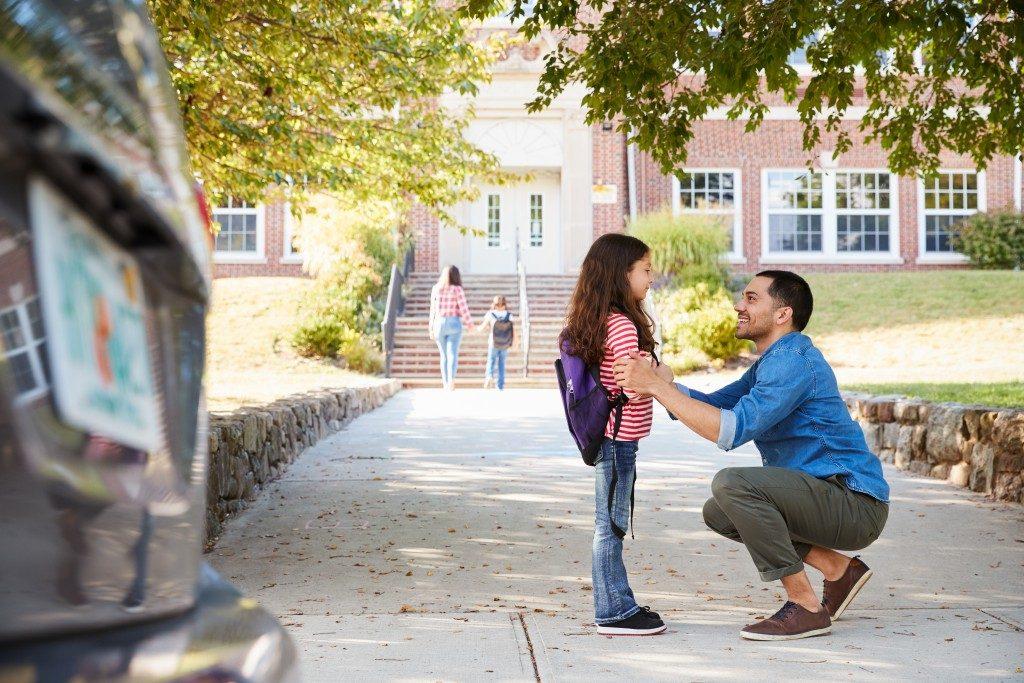Dad sending his daughter to school