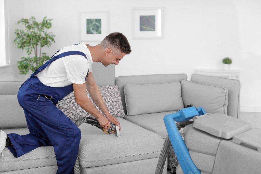 Man vaccuming a sofa
