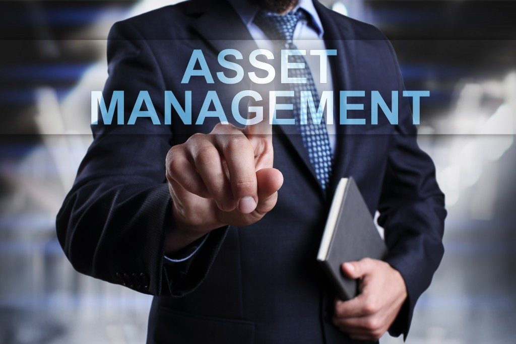 businessman pressing button on touch screen interface and select asset management