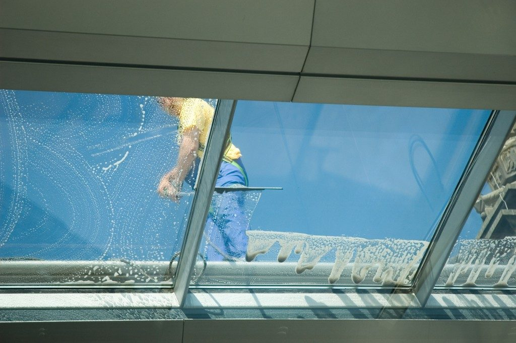 Worker cleaning the building's window