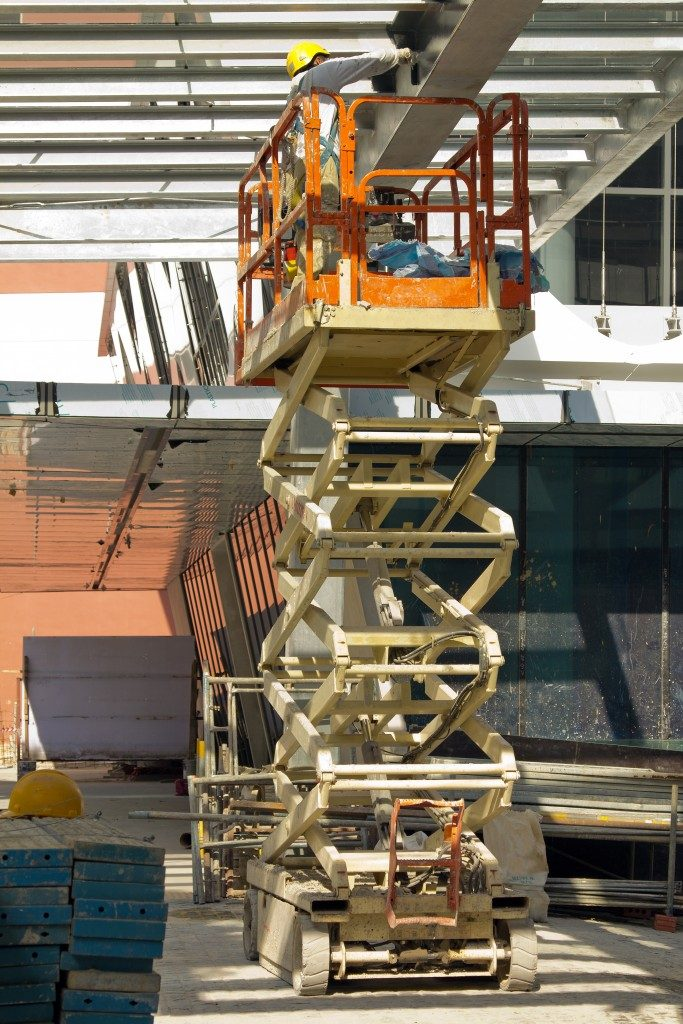 Construction worker Painting Beam using Hydraulic Scissor Lift