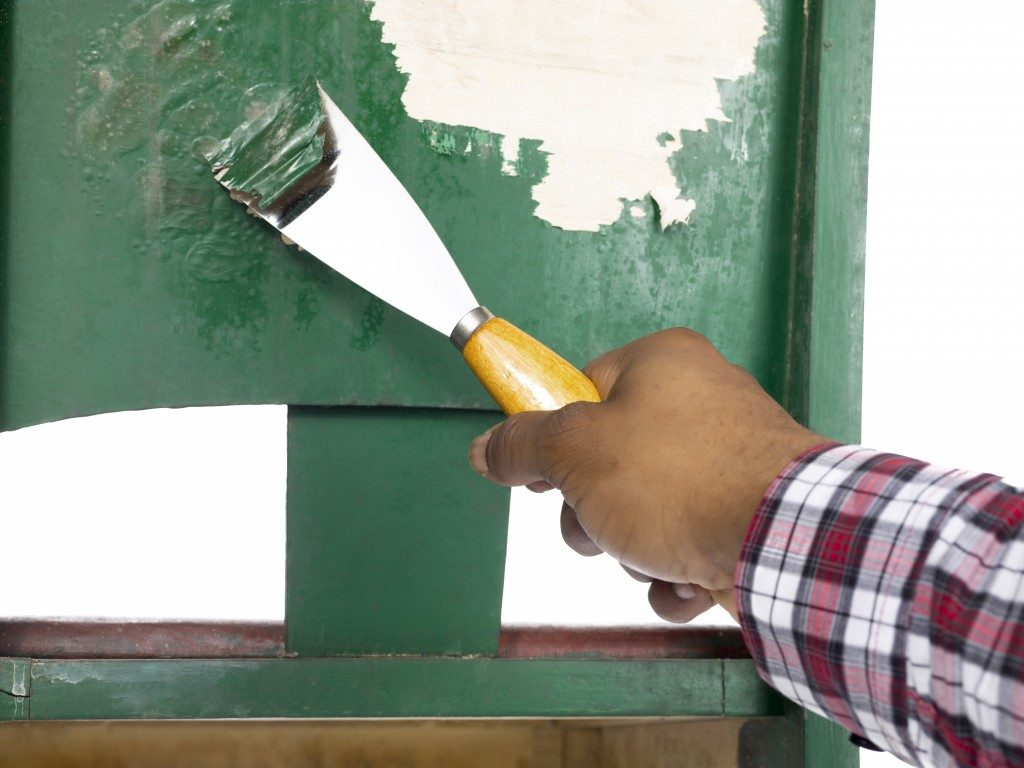 Close-up of man's hand peeling a green paint
