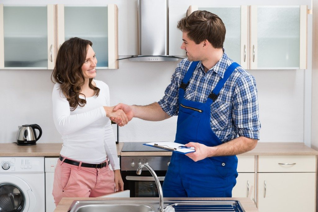 Homeowner shaking hands with a plumber