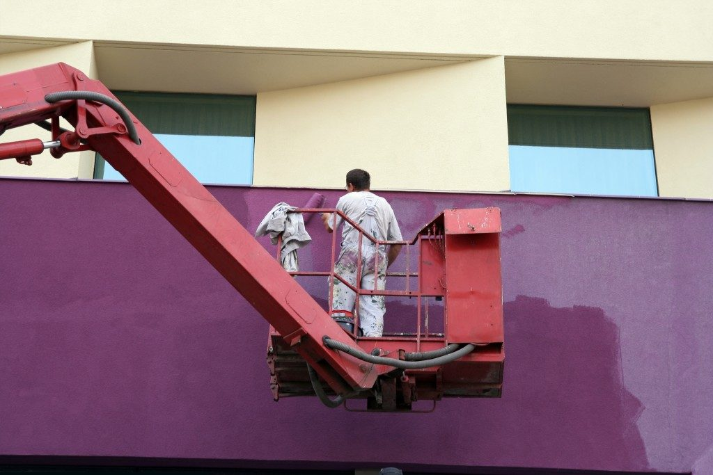 worker riding lift painting wall