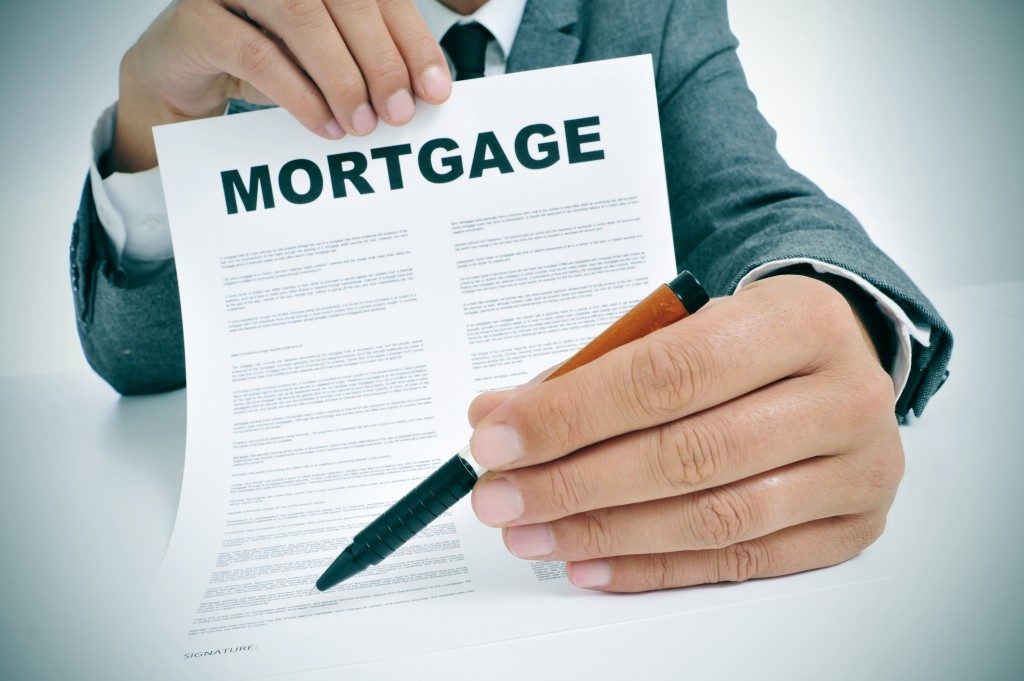 Man showing where to sign on mortgage form