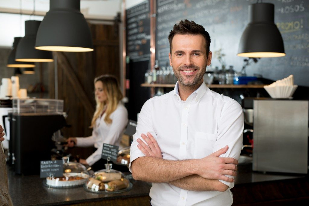 restaurant owner standing in front of the counter