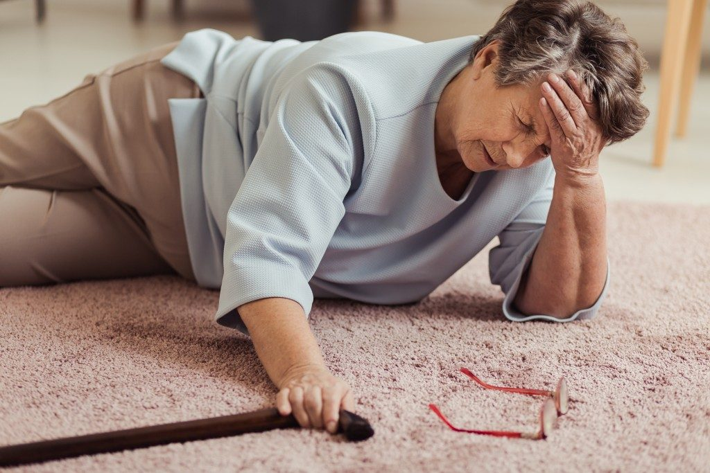 an old woman stumbled on the floor holding her walking stick
