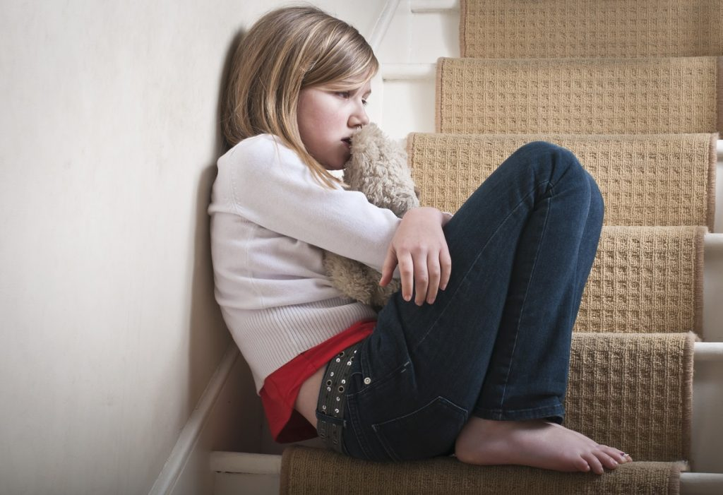 Sad little girl sitting against the wall in despair