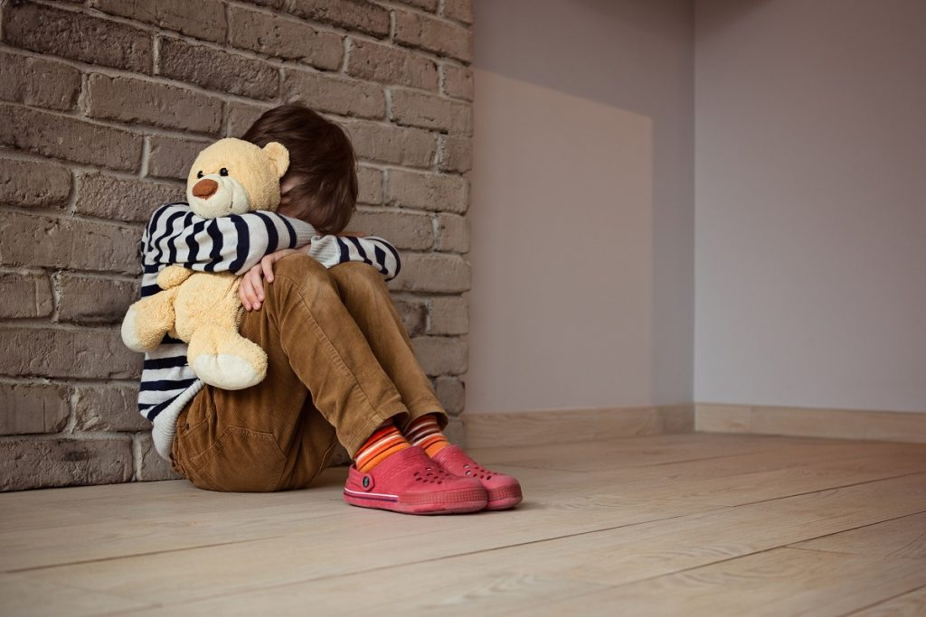 Sad little boy sitting against the wall in despair. In his hands he holds an old friend teddy bear