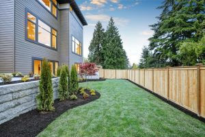 Nice backyard landscape with well kept lawn, flower beds and wooden fence