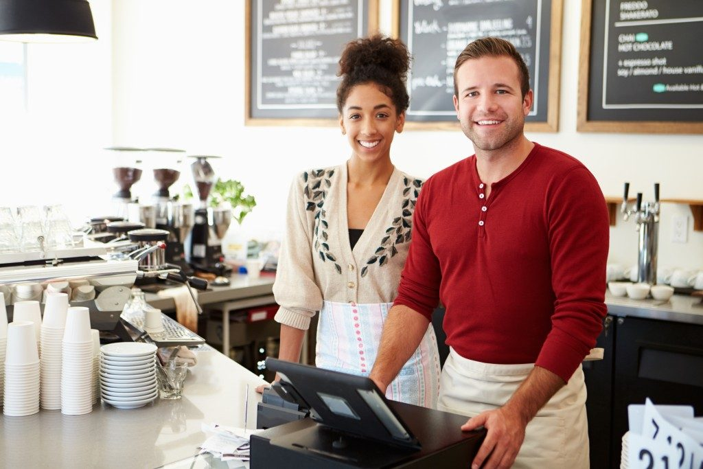 employee and employer standing in front of the counter