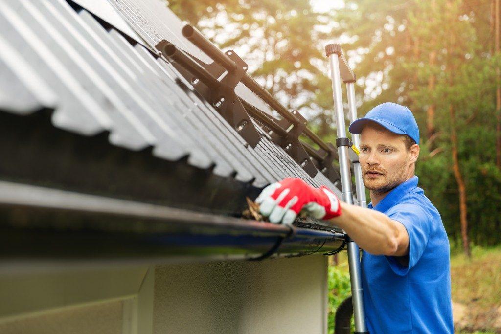 man repairing rain gutter