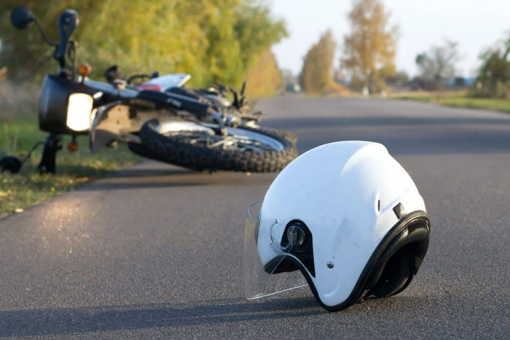 Close up of helmet on the road with crashed motorcycle in the background
