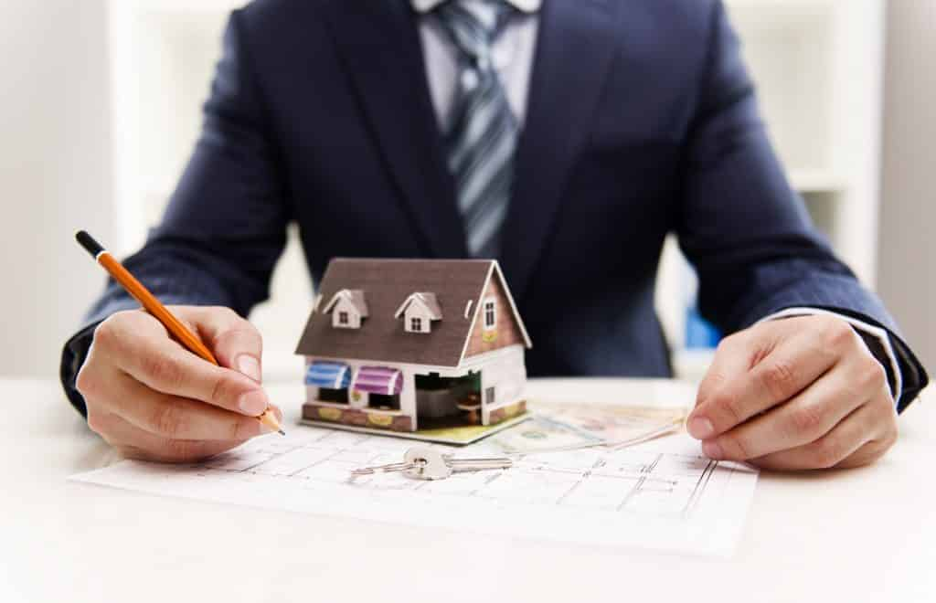 broker holding a pen with a house miniature on top of a document