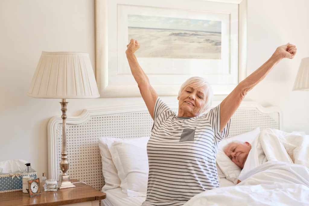 Senior woman sitting on her bed in the morning yawning with arms raised in a stretch